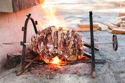 fresh lamb meat on an open fire on a skewer for roasting-jack. daylight, wooden blocks are visible in the background