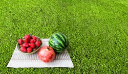 Fresh large strawberries in a wicker basket. Fruits and berries on the lawn with well-groomed grass. A small green watermelon and a large red pomegranate. Light breakfast on the grass.