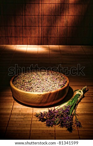 Fresh lavender flower wisps in a bunch and dried aromatherapy scented seeds in a wood bowl over a bamboo mat