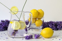 Fresh lavender lemonade served in a glass jar with lemon slices. Summer fruit cold drink from water, lemons and lavender flowers. Fruit still life with lavander lemonade in a pitcher and whole lemons.