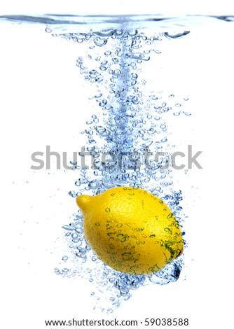 Fresh lemon dropped into water - stock photo