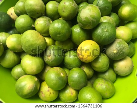 fresh lemon green lemon yellow in the bowl it is healthy food a lot of lemon green lime many lime background fruit Crop group of green fresh lemon  nature food  vitamin c good health