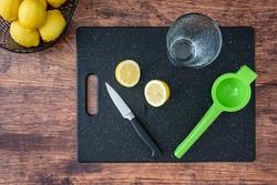 Fresh lemon halves on a black cutting board, paring knife, wood table, basket of lemons, citrus squeezer, drinking glass