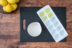 Fresh lemon juice in an ice cube tray, black cutting board, wood table, basket of lemons, white bowl