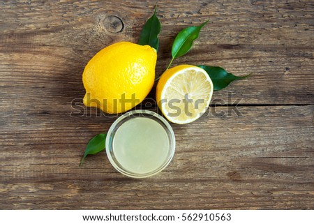 Fresh lemon juice in small bowl and lemons over rustic wooden background with copy space - healthy ingredient for cooking and baking #562910563