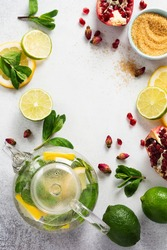 Fresh lemon, lime, pomegranate, dried tea rose flowers, tea, cane sugar, mint leaves and glass teapot on gray background. Ingredients for making cold refreshing fruit tea. Top view.