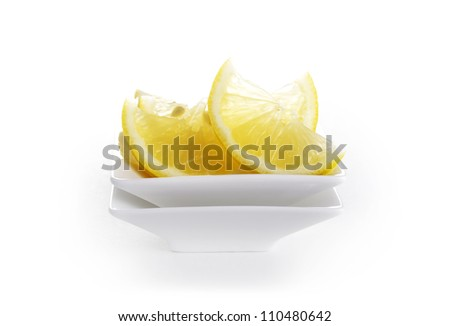 Fresh lemon wedges in small square dish with copy space