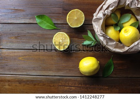Fresh lemon with leaves. Lemon tree. Pannier of yellow lemons with fresh lemon tree leaves on wooden background. Flat lay concept. Copy space.