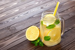 fresh lemonade in mason jar with straw on a wooden table