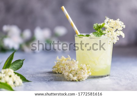 Fresh lemonade with lemon, lime juice and elderberry flowers. Healthy organic homemade refreshing nonalcoholic lemonade mocktail made of elderflower cordial juice. With a paper straw. Gray background.