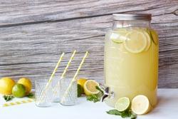 Fresh lemonade with lemons and lime in the beverage dispenser
