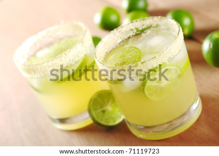 Fresh lemonade with lime slices and ice cubes in a sugar rimmed glass surrounded by limes on wood (Very Shallow Depth of Field, Focus on part of the sugar rim of the first glass)