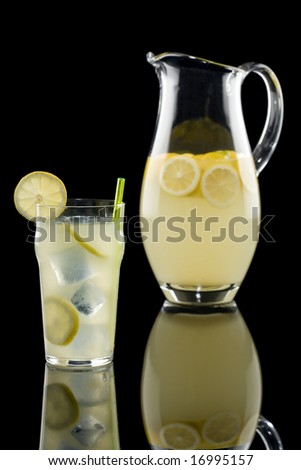 Fresh lemonade with pitcher isolated on a black background