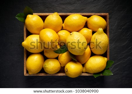 Fresh lemons in a wooden container on a black stone background, top view #1038040900
