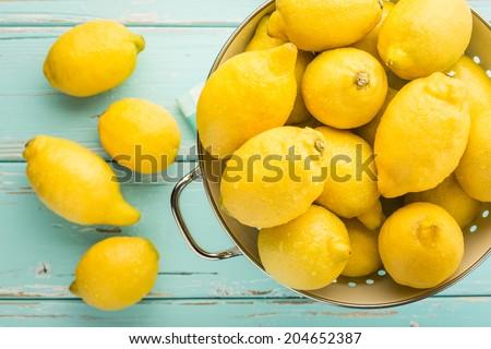 Fresh lemons in retro colander. - stock photo