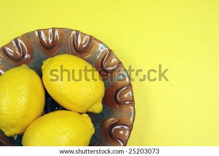 Fresh lemons on decorative purple plate with yellow background