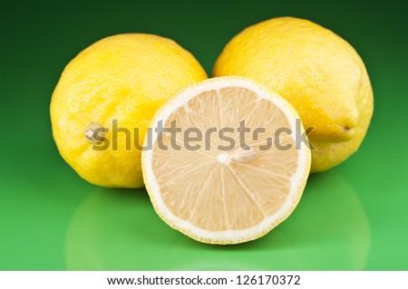 fresh lemons on green background