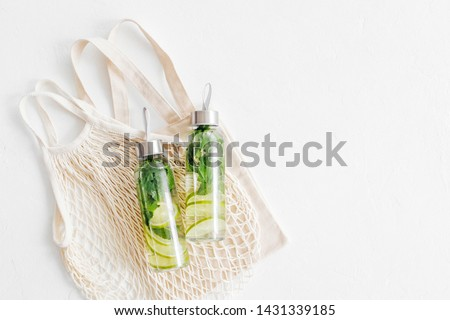 Fresh lime and mint infused water, cocktail, detox drink, lemonade in reusable bottles with eco bags. Eco friendly. Sustainable lifestyle. #1431339185