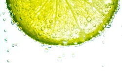 Fresh Lime With Soda Water, Lime Splashing Into Glass Of Water On White Background