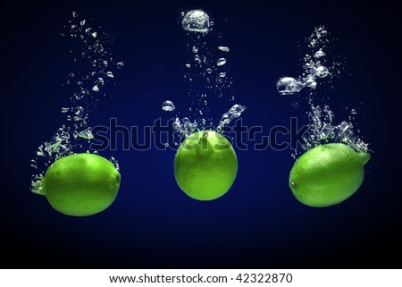 Fresh limes dropped into water with bubbles