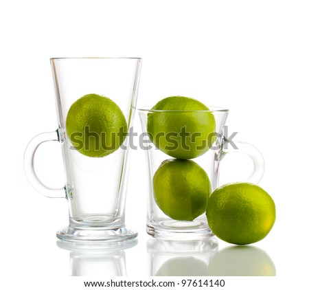 Fresh limes in glass cups isolated on white