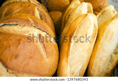 Fresh loaf of white bread. White bread on the showcase in the bakery. Hot baking. Bakery products made from wheat flour. Selective focus image, background, copy space.  #1397680343