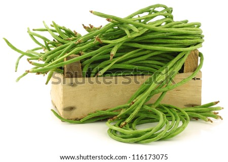 fresh long beans(Vigna unguiculata subsp. sesquipedalis) in a wooden crate on a white background