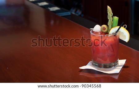 fresh made bloody mary at the bar garnished with olives, onions, asparagus and celery