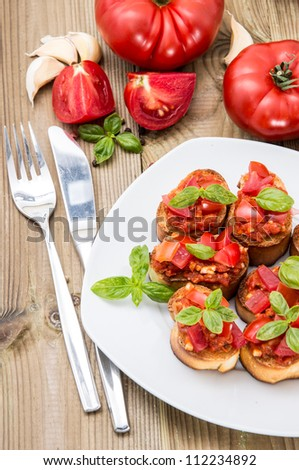 Fresh made Bruschetta on a plate against wooden background