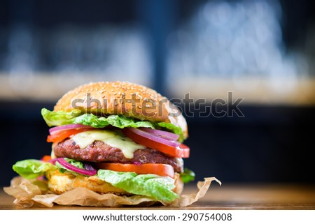 Fresh made cheeseburger with lettuce, tomato and onion.