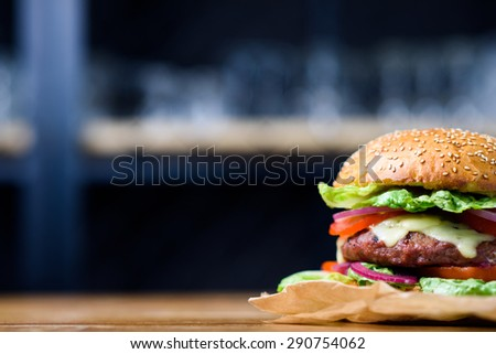 Fresh made cheeseburger with tomato, lettuce and onion.