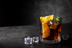 Fresh made Cuba Libre cocktail with brown rum, cola and lemon on wooden background