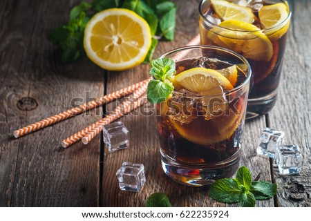 Fresh made Cuba Libre with brown rum, cola, mint and lemon on wooden background Photo stock ©