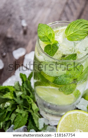 Fresh made Mojito with ingredients on wooden background