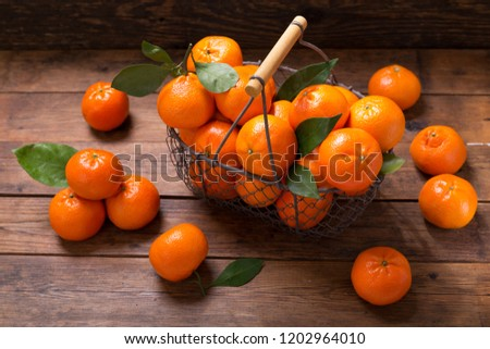 Fresh mandarin oranges fruit or tangerines with leaves in a basket on wooden table #1202964010