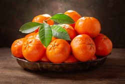 Fresh mandarin oranges fruit or tangerines with leaves in a bowl on wooden table