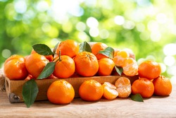 Fresh mandarin oranges fruit or tangerines with leaves in a wooden box over green blurred background