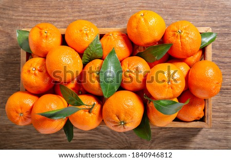 Fresh mandarin oranges fruit or tangerines with leaves in a wooden box, top view ストックフォト ©