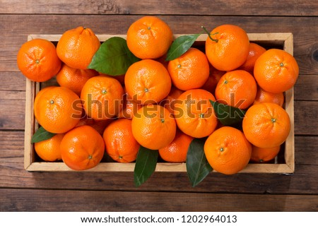 Fresh mandarin oranges fruit or tangerines with leaves in wooden box, top view #1202964013