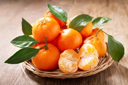 Fresh mandarin oranges fruit or tangerines with leaves on a wooden table