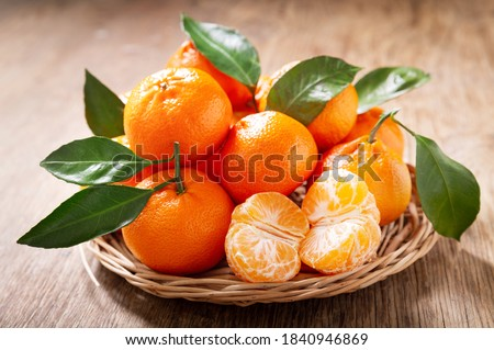 Fresh mandarin oranges fruit or tangerines with leaves on a wooden table ストックフォト ©