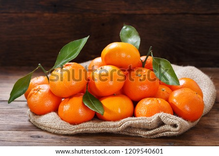 Fresh mandarin oranges fruit or tangerines with leaves on wooden table #1209540601