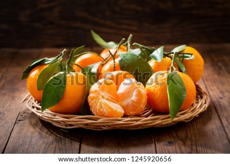 Fresh mandarin oranges fruit or tangerines with leaves on wooden table #1245920656