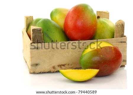 fresh mango fruit and a cut one in a wooden box on a white background