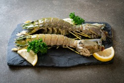 fresh mantis shrimp with lemon on black board
