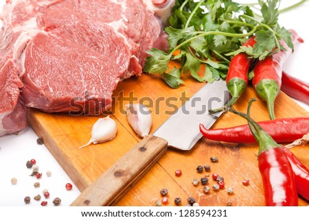fresh meat of beef with bone on wooden with spices and knife