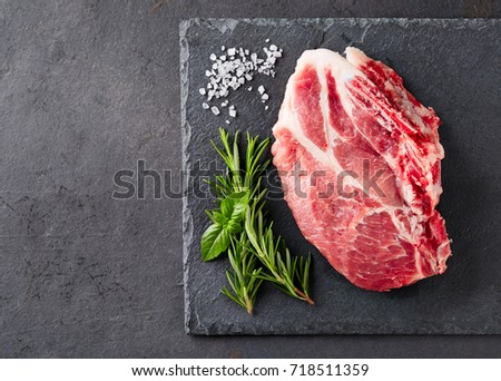 Fresh meat with herbs on a graphite background
