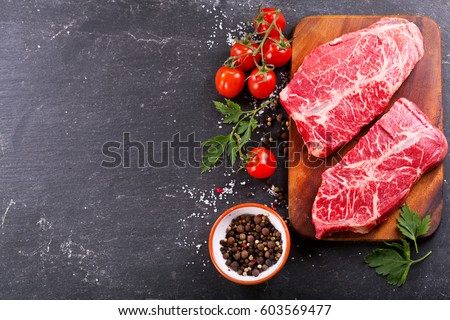 fresh meat  with ingredients for cooking on dark background