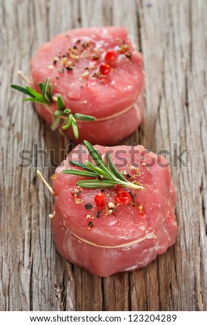 Fresh meat with spices and rosemary on a wooden background.