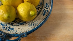 Fresh Mediterranean lemons on a beautiful blue and beige patina painted antique ceramic plate on wooden background. Close up.
